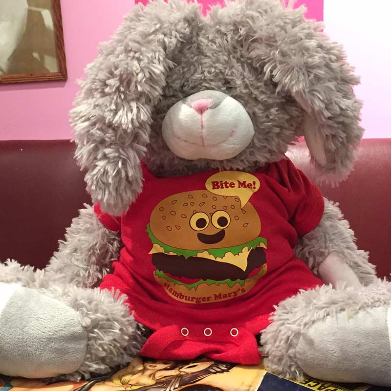 stuffed animal bunny wearing a red onesie with a hamburger on it saying bite me